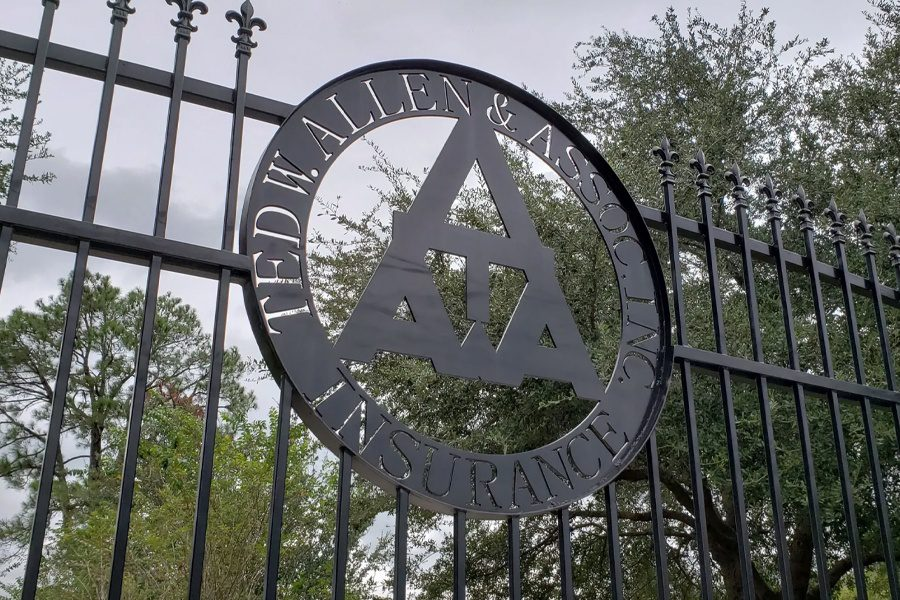 Cypress, TX - Closeup Angled View of Rod Iron Gate With Ted W. Allen & Associates, Inc. Logo in Center