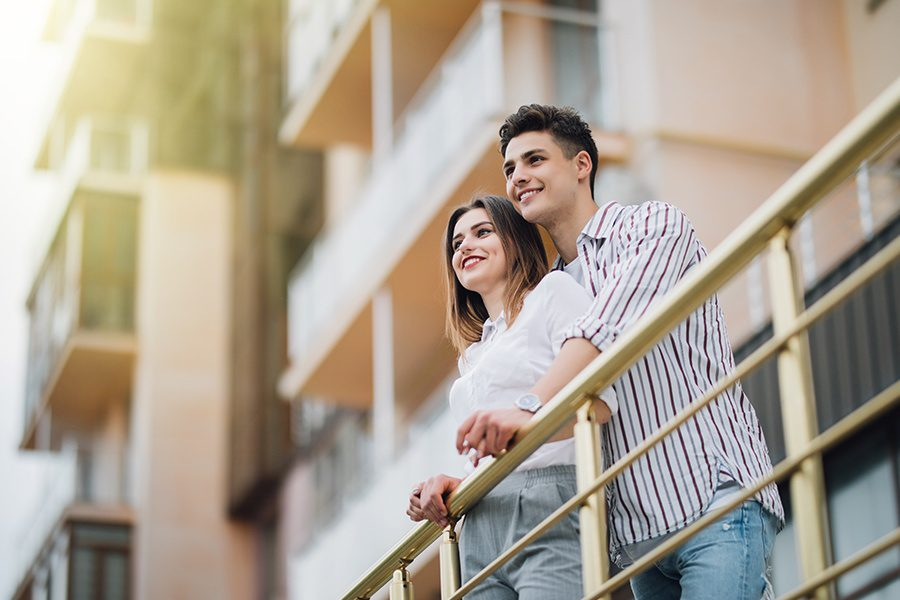 Habitational Risks - Happy Couple Relaxing and Having Fun on the Balcony of Their New Apartment