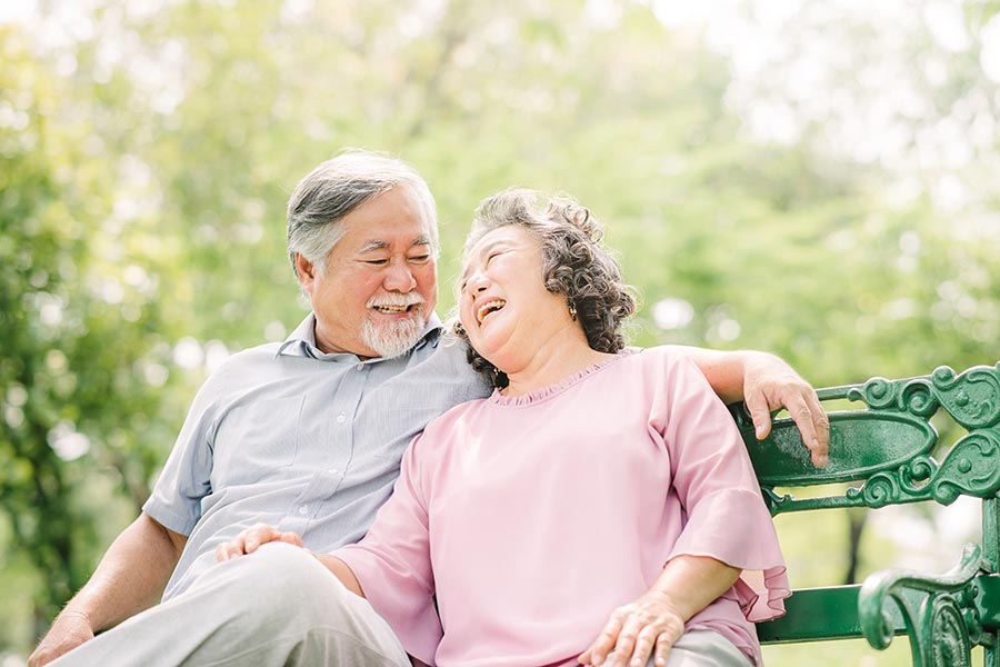 About Our Agency - Senior Couple Laughs Together on a Bench on a Sunny Day in a Park