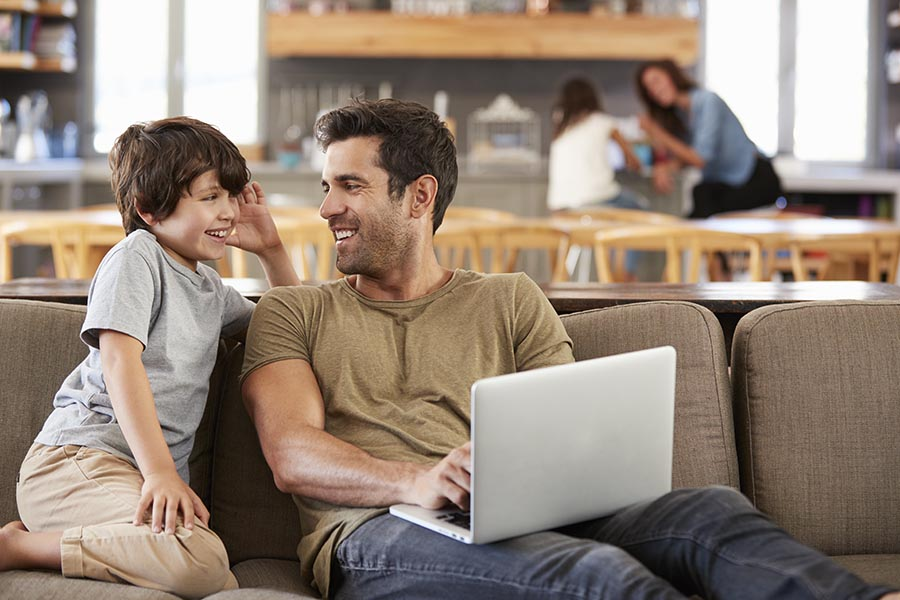 Client Center - Father and Young Son Use a Computer at Their Couch, Mother and Daughter in the Background