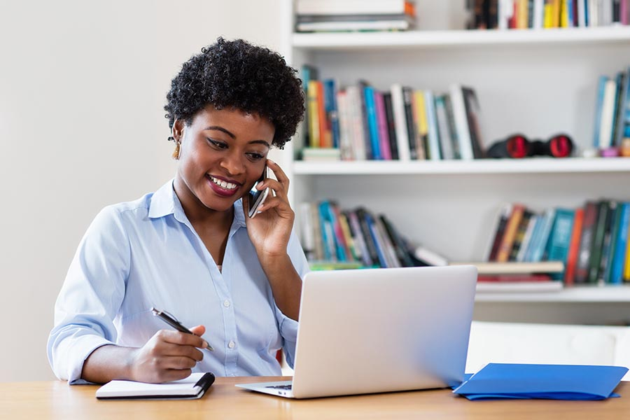 Contact Us - Businesswoman Smiles and Makes a Call While Taking Notes, at Her Desk in a Bright Office
