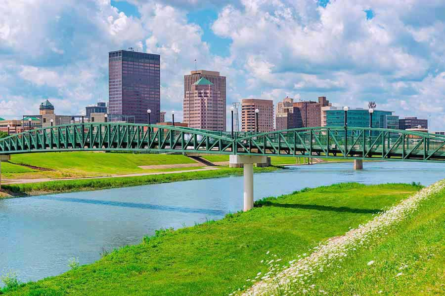 Homepage - View of Dayton, Ohio From a Distance, the Miami River and Green Grass in the Foreground, White Clouds Overhead