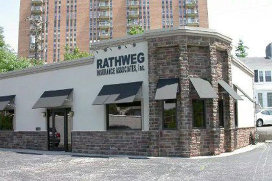 Kettering, OH Insurance - Rathweg Insurance Associates Office Location, a Stucco and Stone Building With Black Awnings Over the Windows