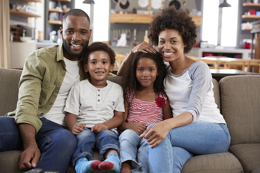 Personal Insurance - Father, Young Son and Daughter, and Mother Sit Close on Their Tan Couch, Comfortable and Smiling