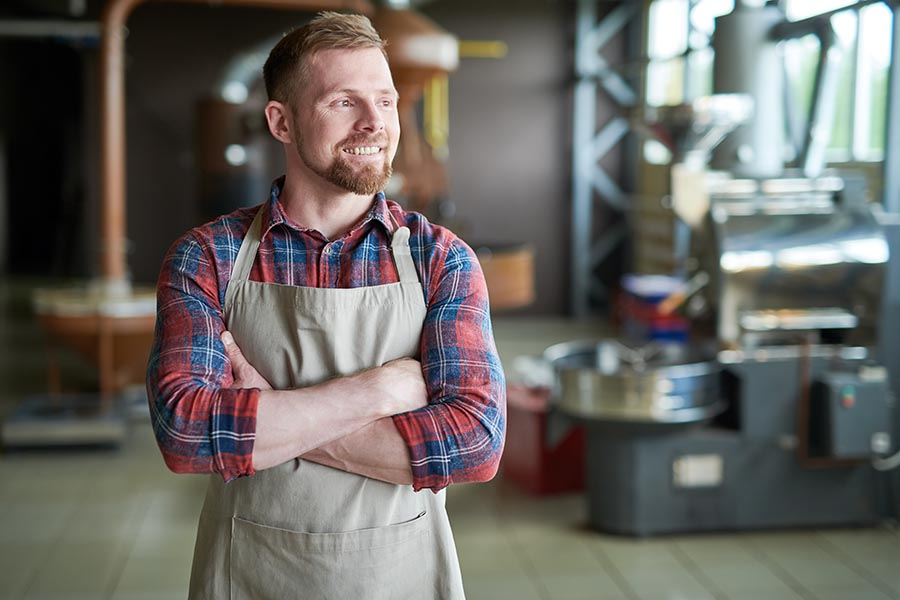 Specialized Business Insurance - Craftsman Poses in His Workshop Wearing a Red Flannel Shirt and Tan Apron