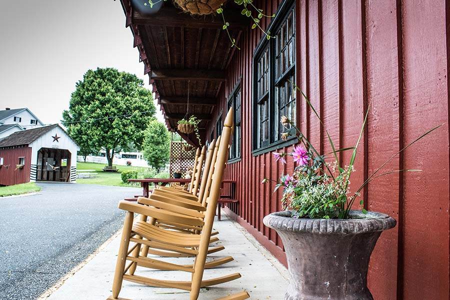 Blog - Closeup View of Wooden Rocking Chairs in Front of a Red Amish Store in Lancaster Pennsylvania