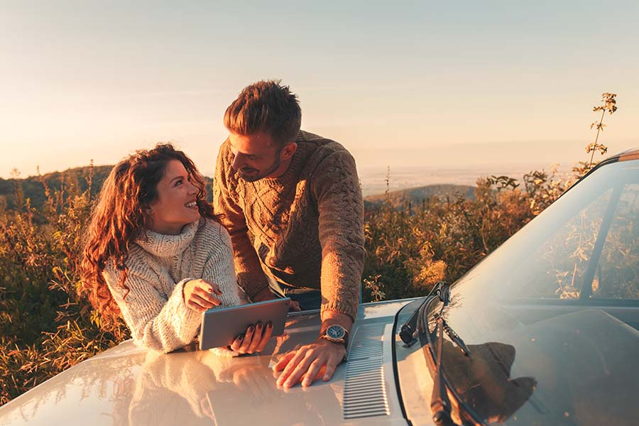 Client Center - View of Young Couple on a Road Trip During Sunset Leaning Against Their Car While Using a Tablet