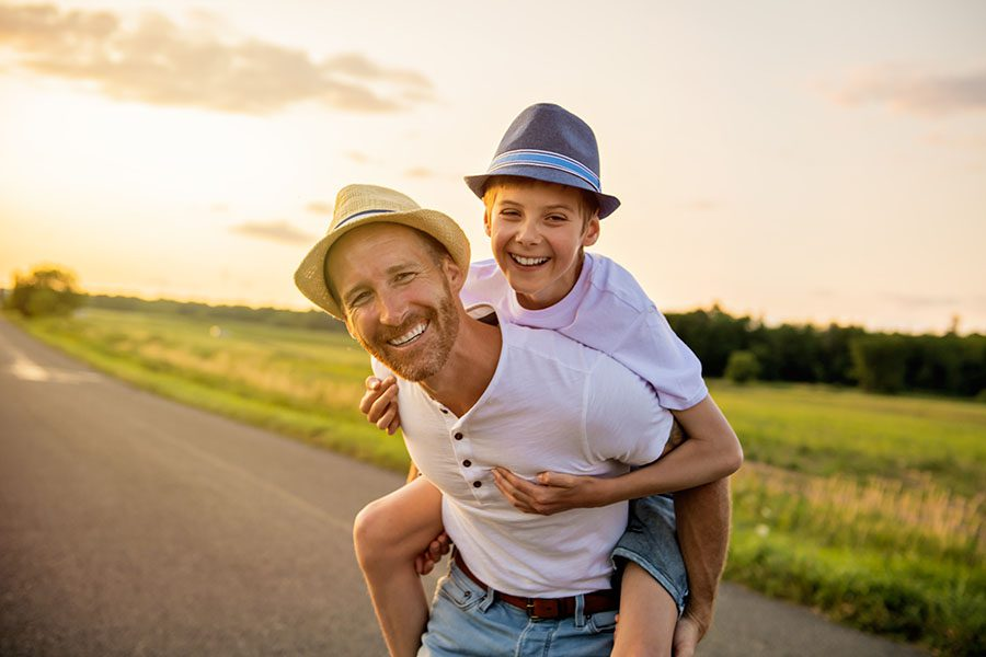 Contact - Cheerful Father Giving His Son a Piggyback Ride on an Empty Country Road at Sunset