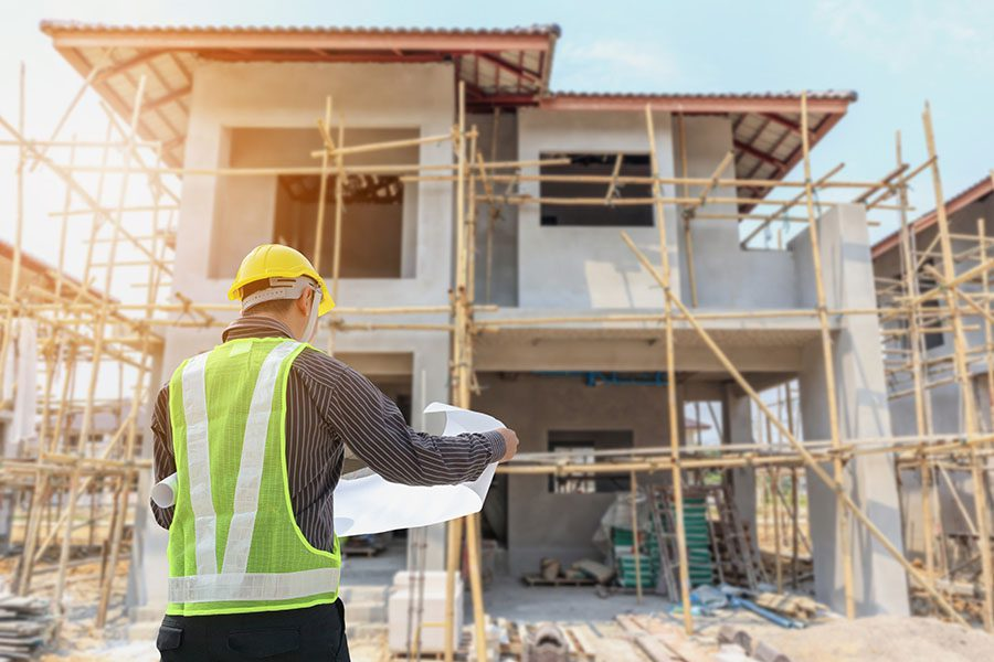 Specialized Business Insurance - View of Contractor Analyzing House Blueprints While Standing on a Residential Construction Jobsite