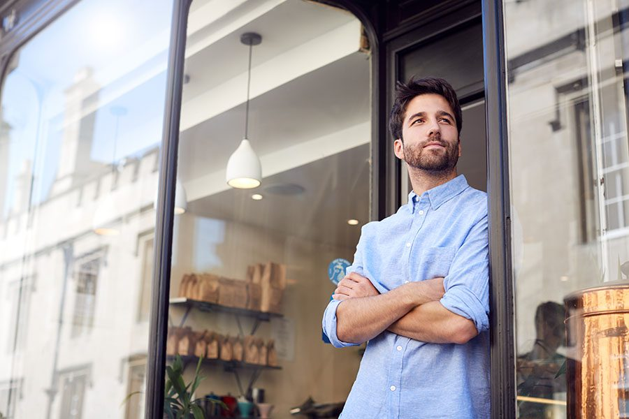 Business Insurance - Portrait of Young Small Business Owner Standing Next to His Coffee Shop with His Arms Folded in the City