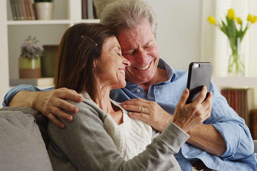 Client Center - Portrait of Smiling Mature Couple Spending Time Together on the Sofa and Using a Cellphone