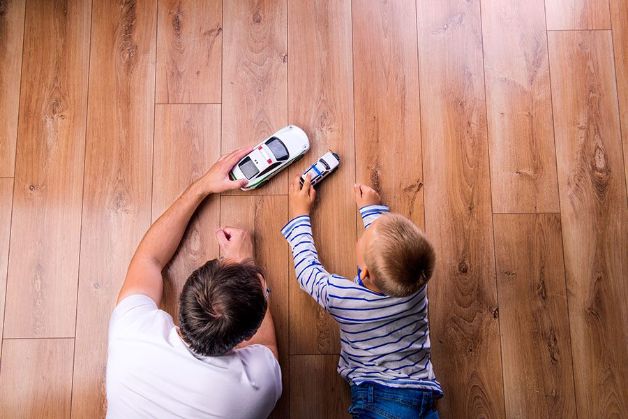 Insurance Quote - View of Father and Son Playing with Toy Cars Across a Wooden Floor at Home