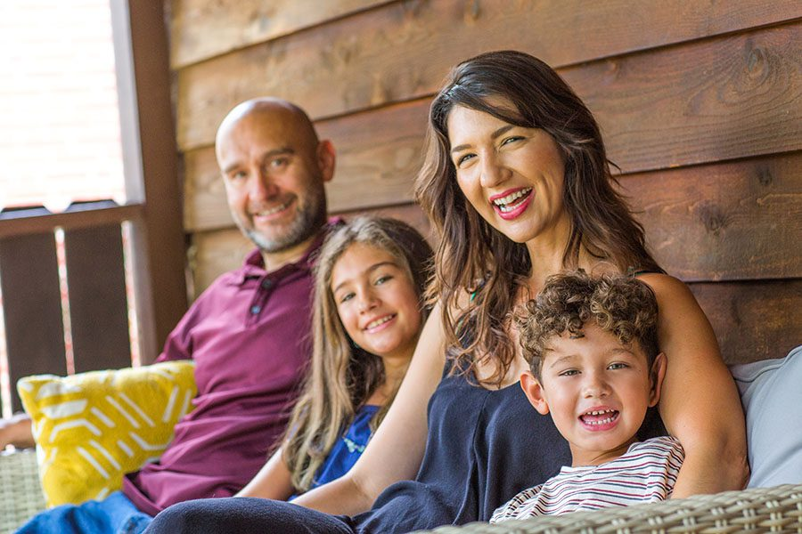 Personal Insurance - Closeup View of Cheerful Family with Two Kids Sitting on Front Porch of Their Home