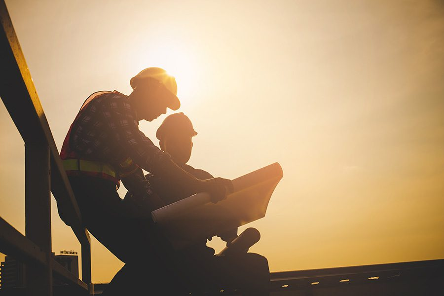 Specialized Business Insurance - Silhouette of Engineer and Contractor Discussing Building Plans While Sitting on a Construction Jobsite at Sunset