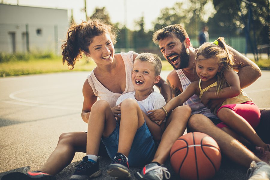 Employee Benefits - Portrait of Family with Two Children After Playing Basketball at a Playground
