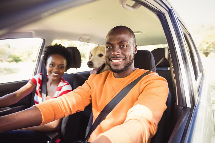 Personal Insurance - Happy Family and Their Dog Posing in Their Car Together Before a Trip