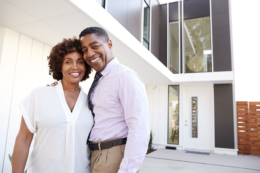 Personal Insurance - Couple Standing Outside and Admiring Their New Modern Home