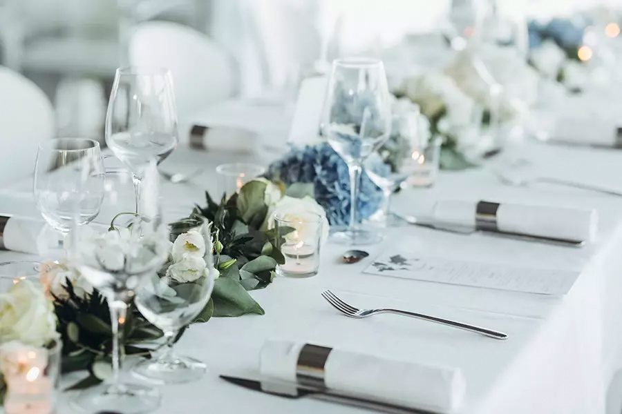 Special-Event-Insurance-Wedding-Table-Decoration-with-Floral-Garland-and-Blue-Flowers-Between-Glasses-on-a-White-Tablecloth