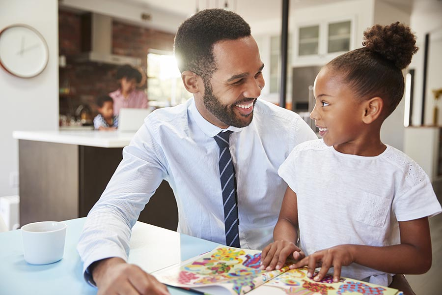 Personal Insurance - Father in a Suit and Tie Smiles at His Young Daughter as They Chat at the Kitchen Table