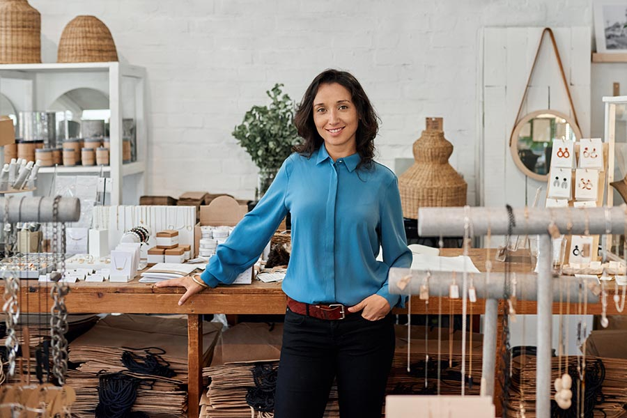Specialized Business Insurance - Shop Owner Stands in Her Independent Retail Store, Clothing and Home Goods on the Shelves