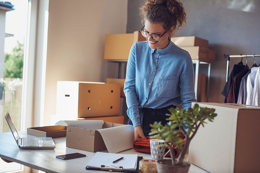 Business Insurance - Smiling Young Small Business Owner Preparing Boxes for Shipping in Her Office