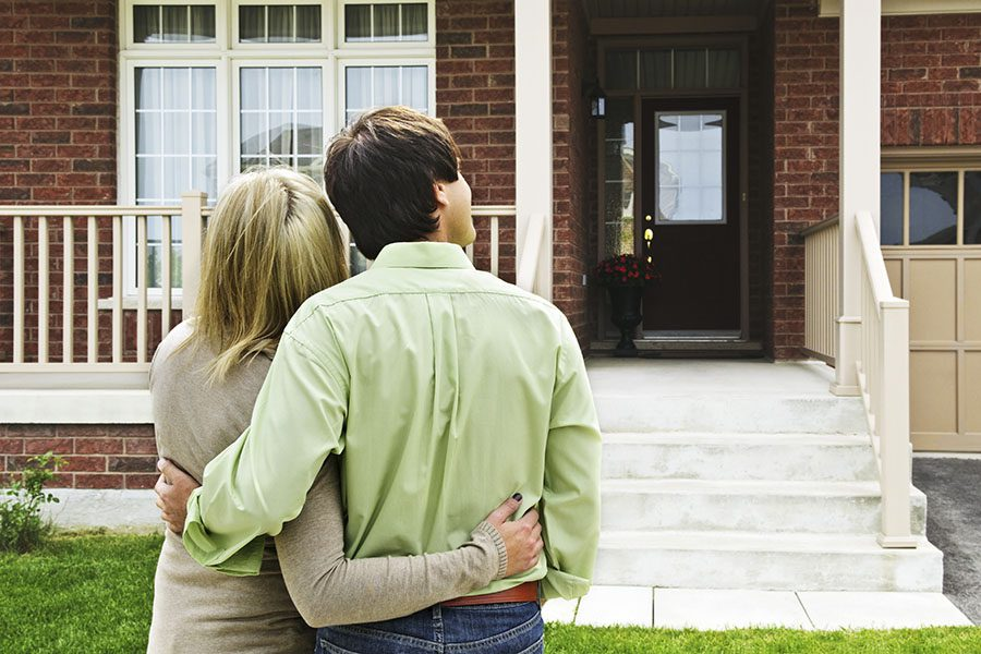Contact - Rear View of a Young Couple Looking at Their New Brick Home