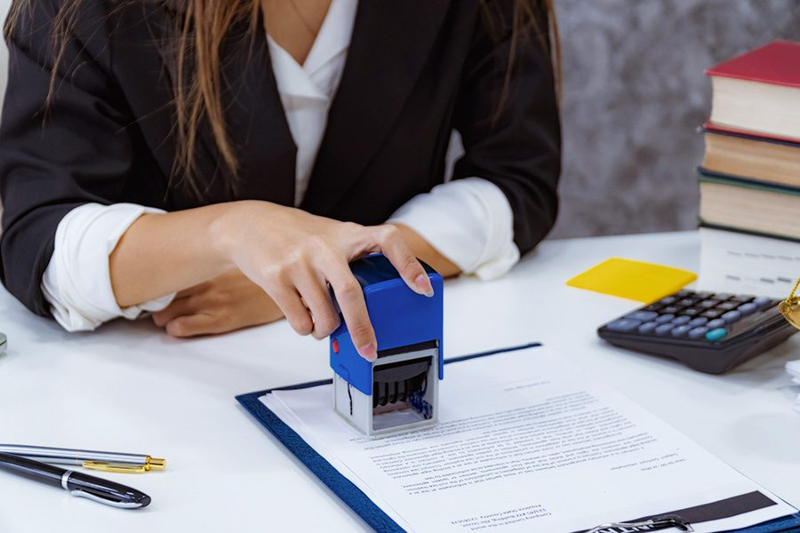 Notary and PennDOT Services - Closeup View of a Business Woman Sitting at Her Desk Stamping a Bunch of Paperwork