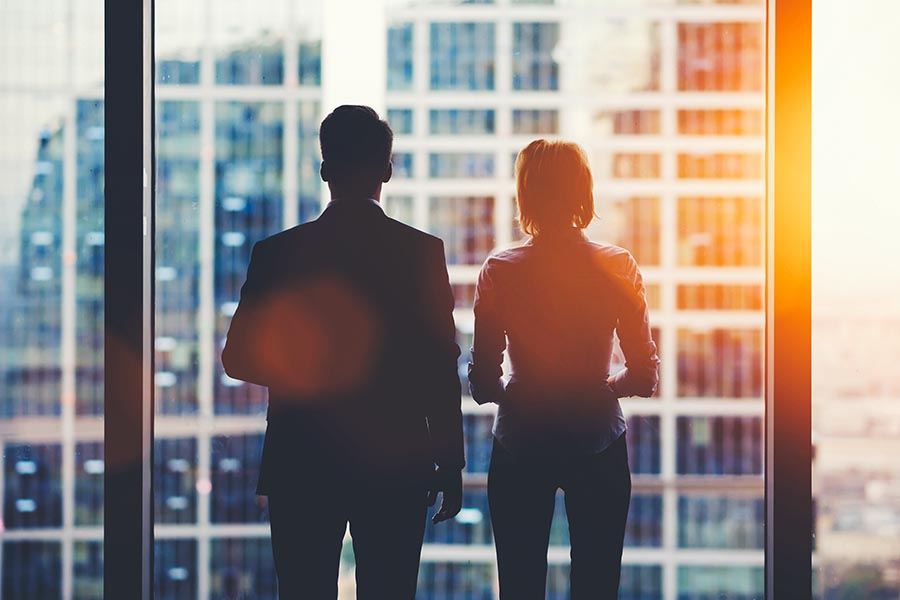 About Our Agency - Two Business Associates Stand in Silhouette Against a Large Window in a Skyscraper, Orange Sunlight Streaming in at Dusk
