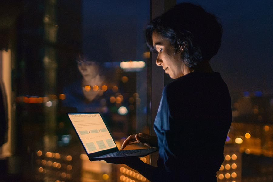 Client Center - Woman Uses a Computer Next to a Large Window at Night With City Lights Glowing Below