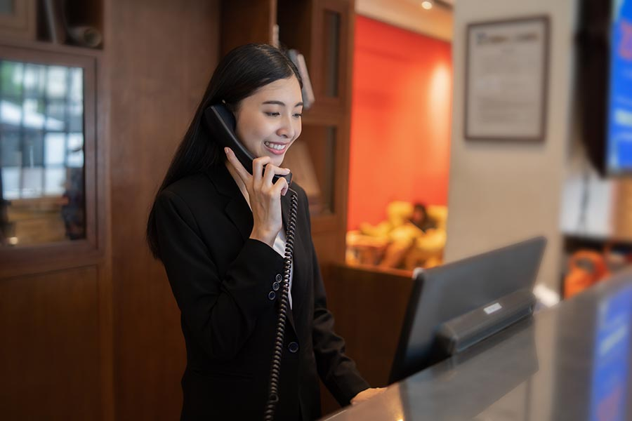 Contact - Hotel Owner Makes a Call at Reception Desk in High End Hotel