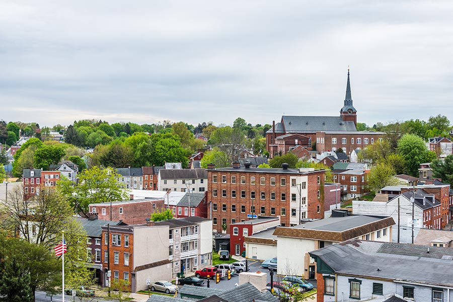 About Our Agency - Pennsylvania Town Seen From Above,With Church Spires, Brick Houses, Green Trees, and an American Flag Waving