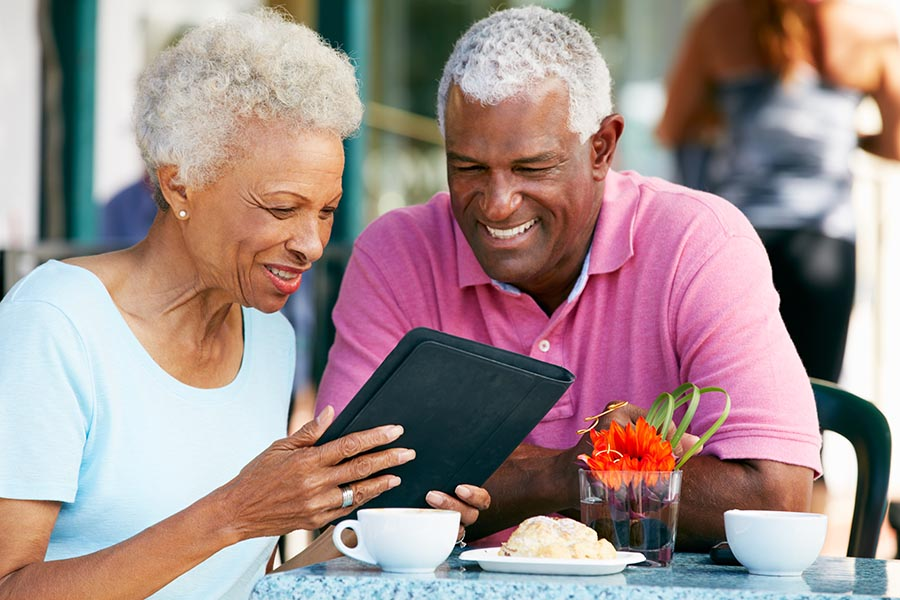 Blog - Senior Couple Reads a Tablet Seated at an Outdoor Table Enjoying Breakfast and Coffee