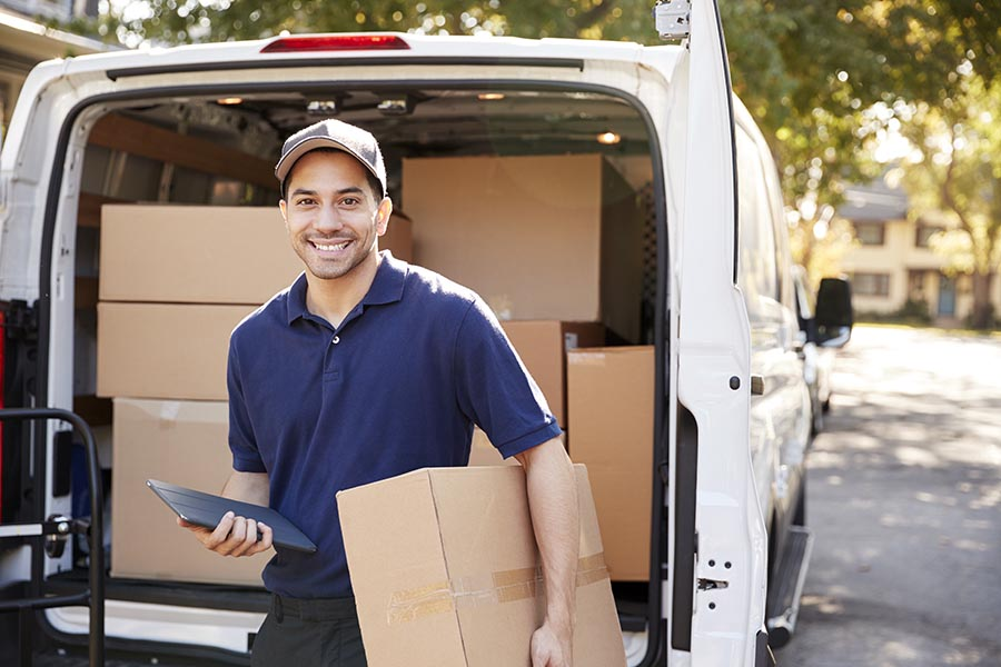 Business Insurance - Courier Smiles as He Prepares to Deliver a Package, a Large White Van Filled With Product Behind Him