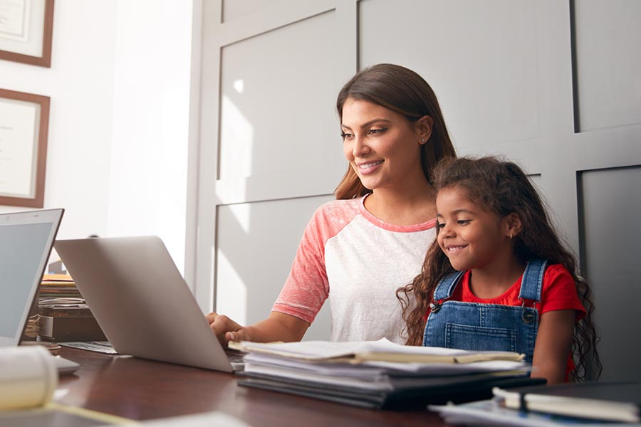 Client Center - Mom and Daughter Sit Together at a Desk, Mom Using the Computer, Paperwork Nearby