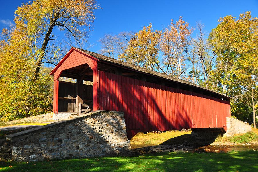 Lancaster, PA - a Red Covered Bridge in Pennsylvania Surrounded by Green Grass and Fall Foliage, a Stream Passing Underneath the Bridge