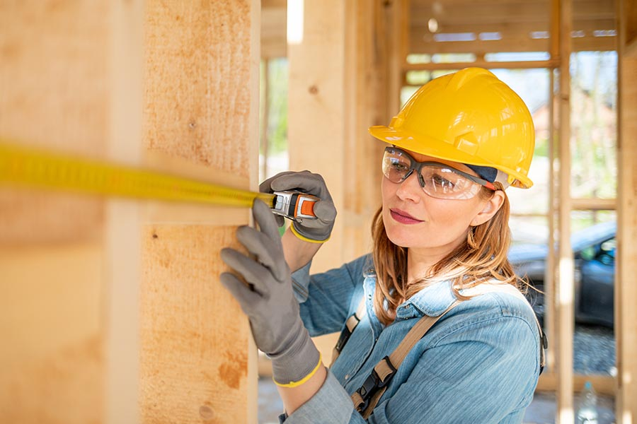 Specialized Business Insurance - Contractor in Hardhat and Safety Goggles Uses a Measuring Tape on a Job Site