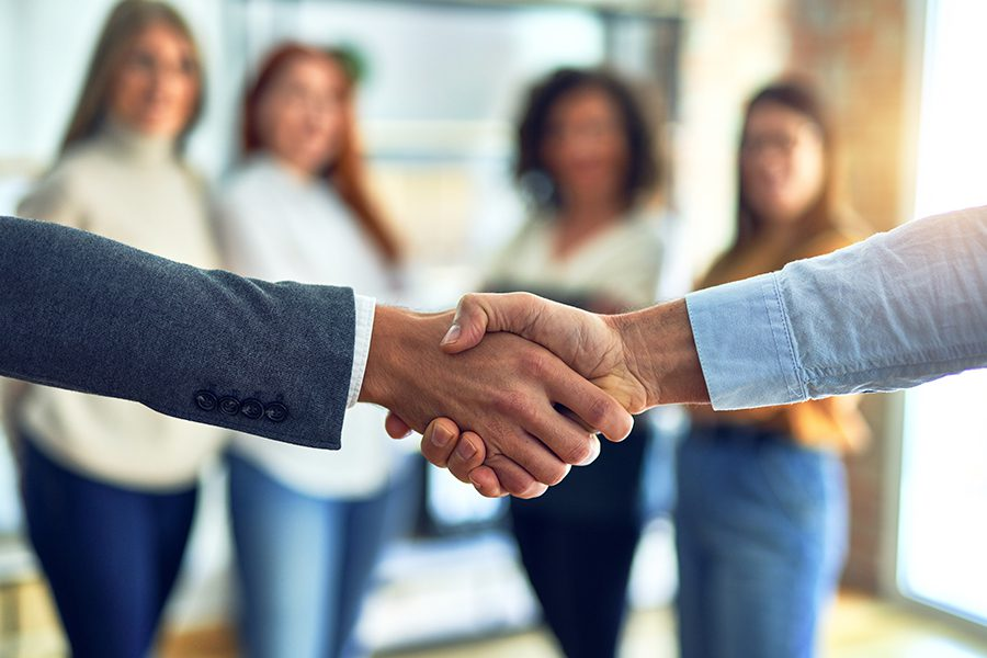 About Our Agency - Group of Business Workers Standing Together and Shaking Hands at the Hometown Insurance Services, LLC Office