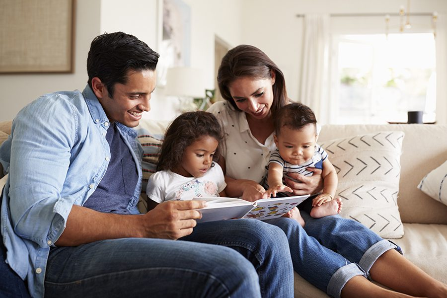 Blog - Family Reading a Book Together on the Sofa in Family Living Room