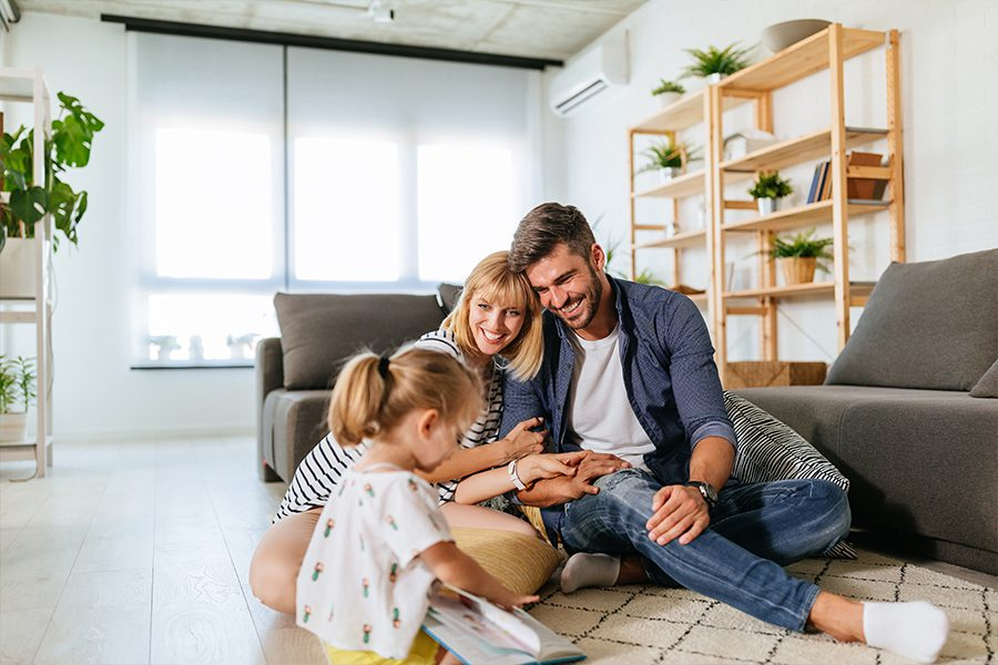 Personal Insurance - Happy Family Enjoying Time Together on the Living Room Floor of Their New Home