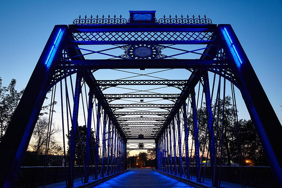 About Our Agency - Wells Street Bridge in Fort Wayne, Indiana, Lit With Blue and Purple Lights, Silhouetted Against a Darkening Sky