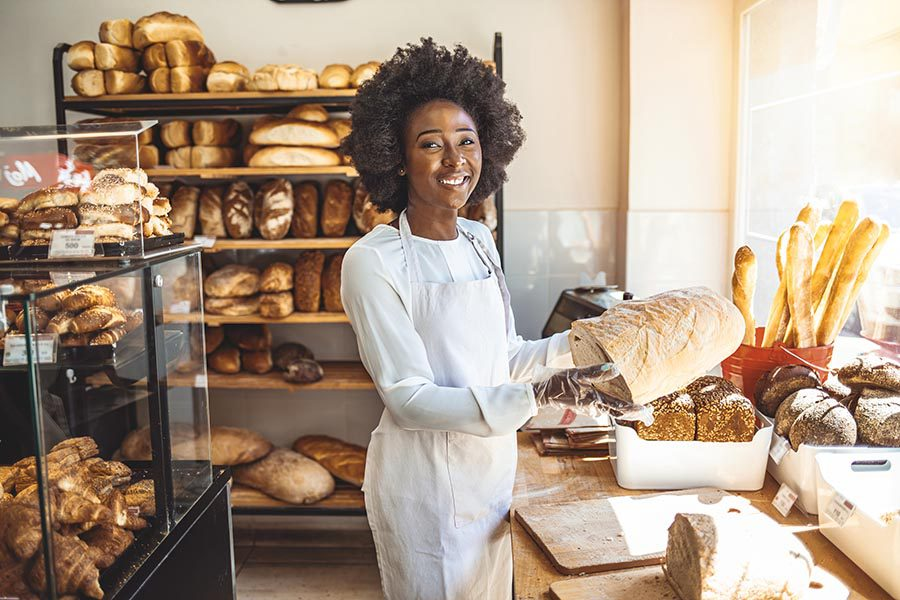 Business Insurance - Young Bakery Owner in Apron Smiles as She Slices Bread, Surrounded by Shelves of Baked Goods and Loaves of Bread