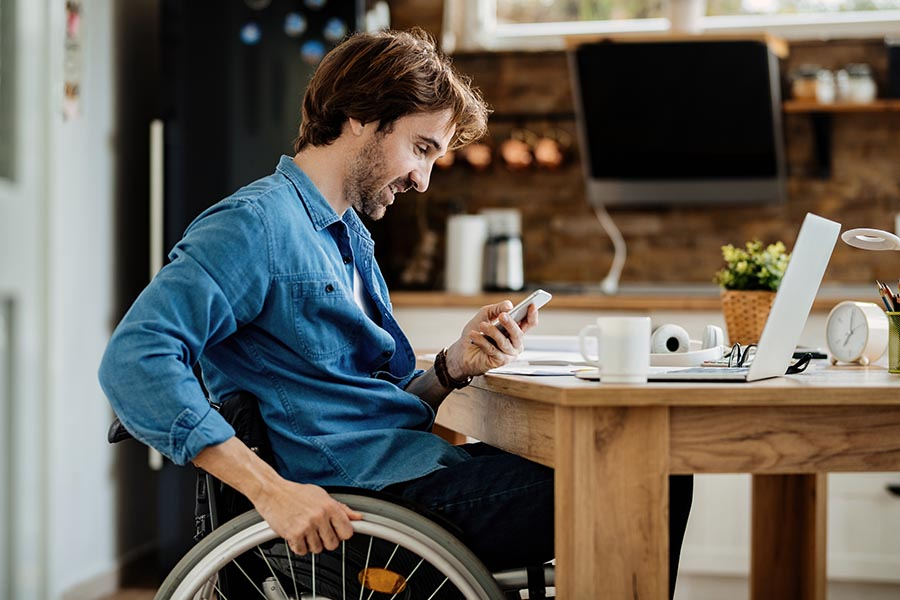 Contact Us - Man in Denim Shirt and Black Wheelchair Smiles and Uses His Phone at His Kitchen Table, Coffee and Laptop Nearby