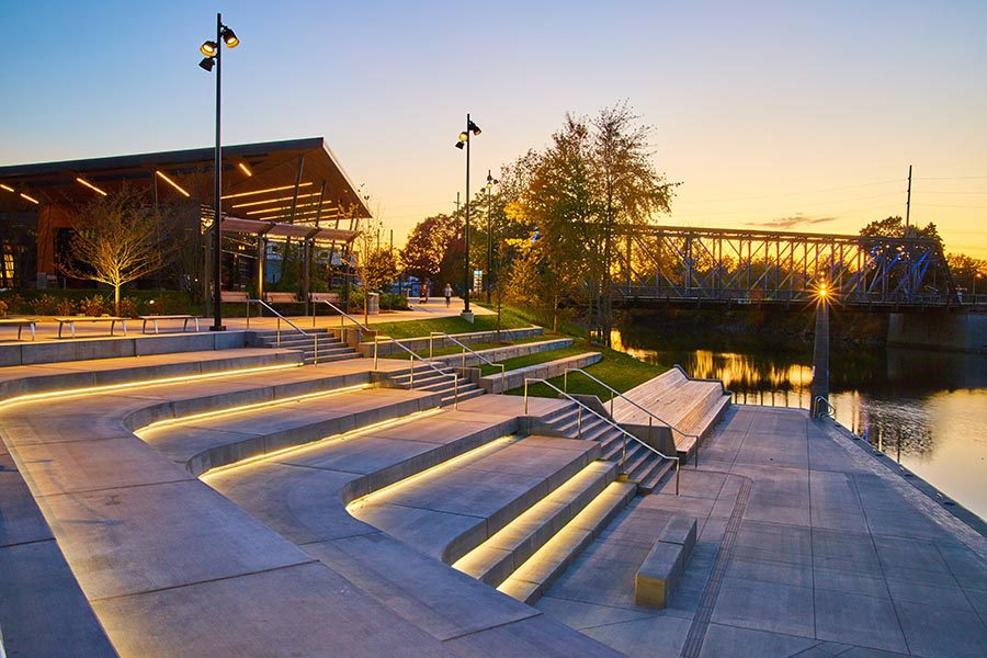 Fort Wayne, IN Insurance - Amphitheater in Fort Wayne, Indiana With Lit up Stairs Leading to the Water, a Bridge Nearby, Sun Setting Churubusco, IN Insurance - Placid Lake Lined With Rocks and Trees on a Cloudless Day