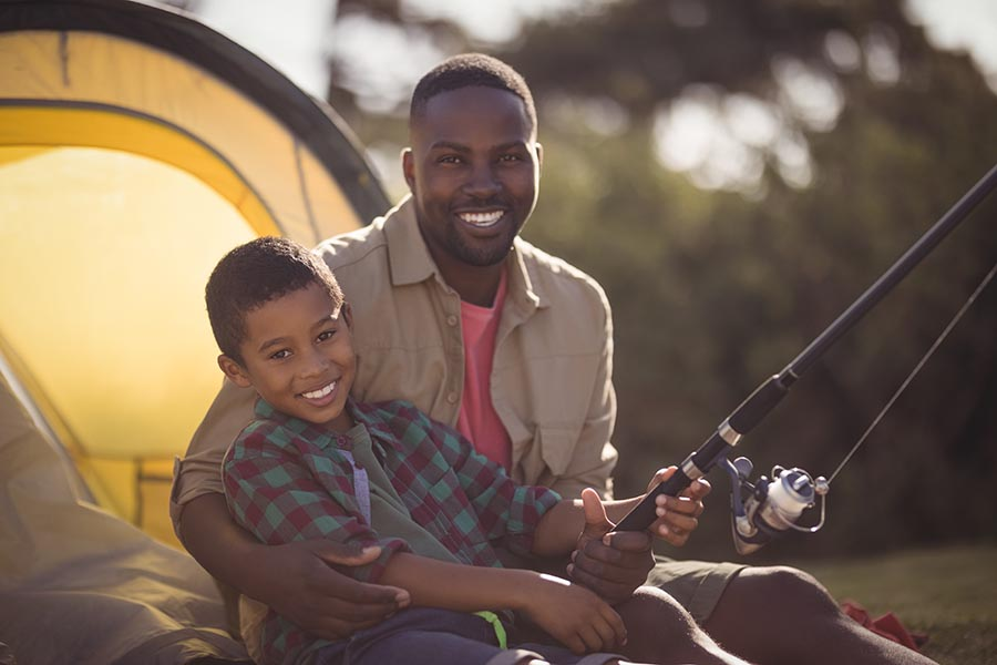 Personal Insurance - Father and Son Fishing Near Their Yellow Tent on a Warm Day, Smiling as Dad Wraps His Arm Around His Young Son