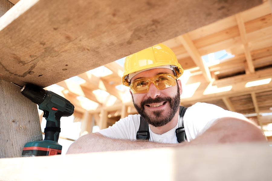 Specialized Business Insurance - Young Contractor Smiles on a Break From Framing a Home, Wearing Safety Goggles and Hard Hat