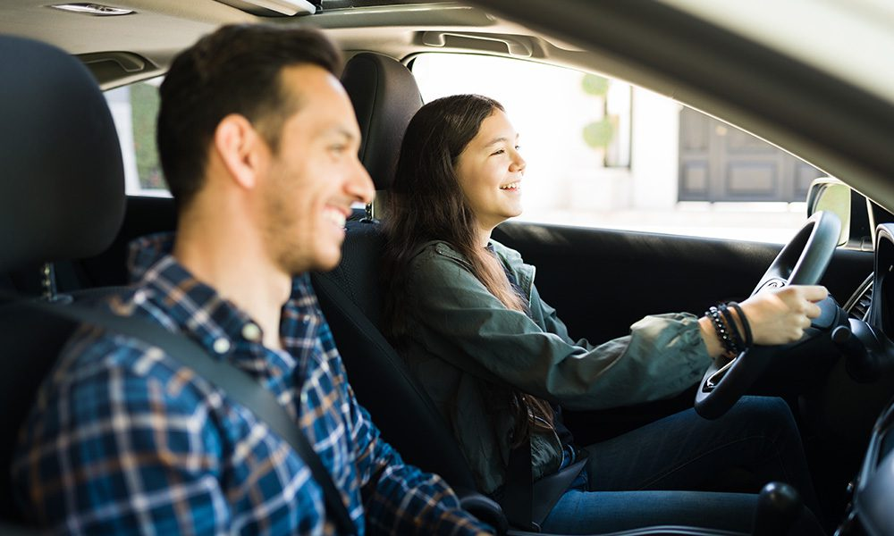 Blog - Dad Teaching Daughter How to Drive on a Sunny Day