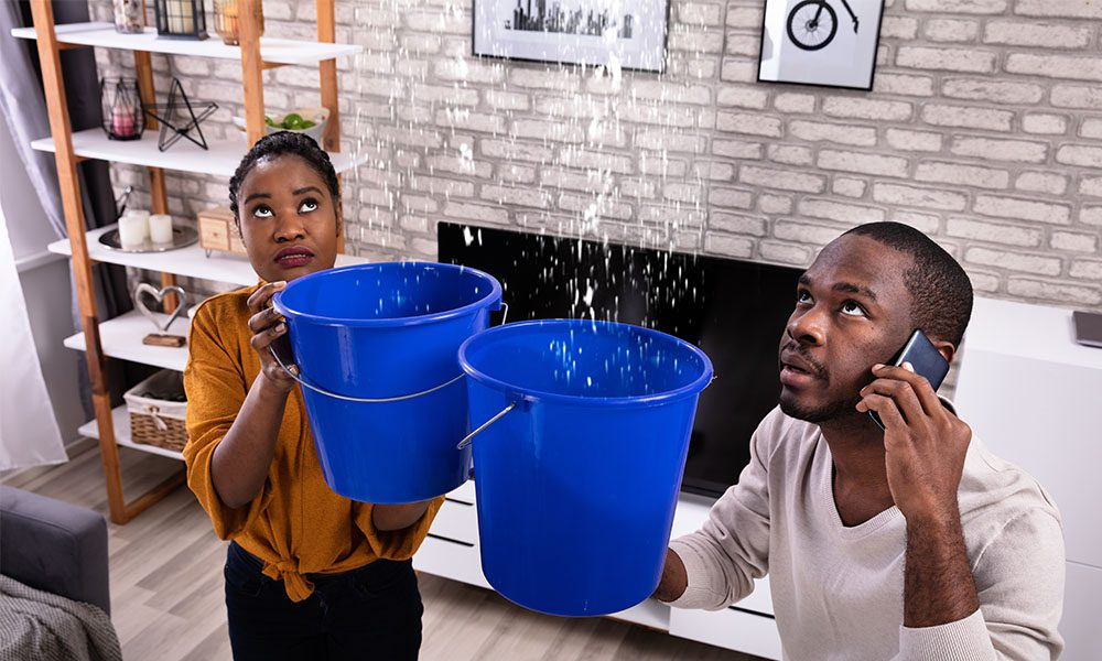 Blog - Couple Standing in Living Room Holding Blue Buckets Under a Dripping Ceiling While on the Phone