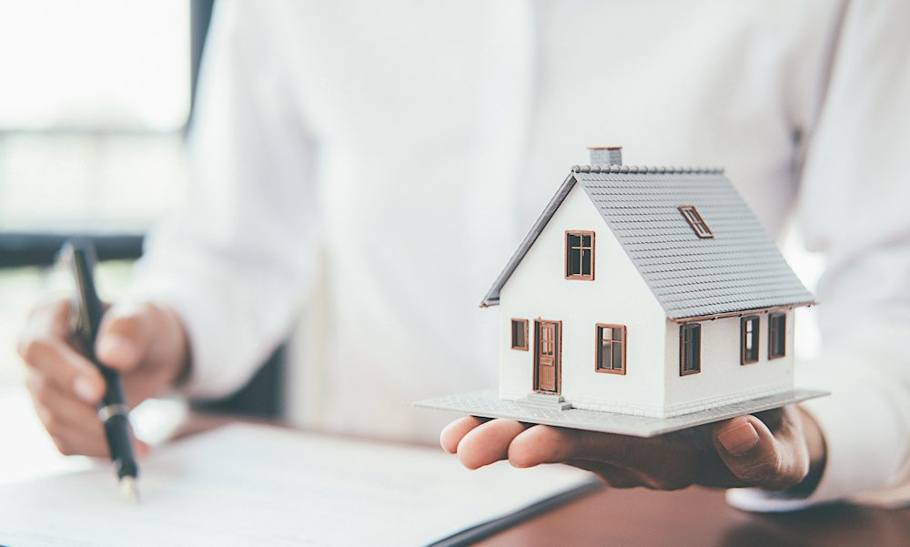 man signing paperwork holding a mini house in his hand