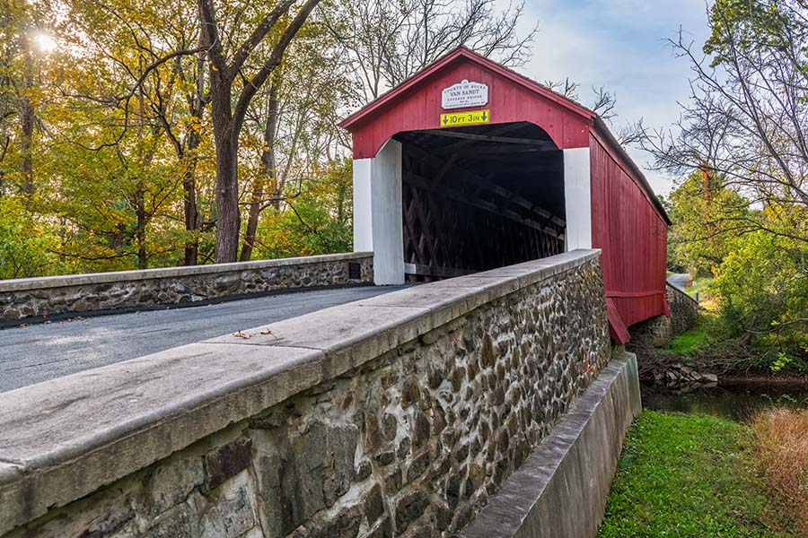 About Our Agency - Closeup View of a Red Covered Bridge Road in Bucks County Pennsylvania on a Sunny Day