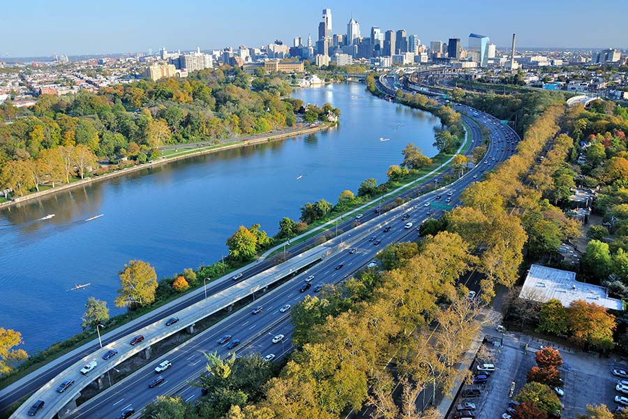 Contact - Aerial View of Philadelphia City Skyline Next to the River with Views of the Highway and Surrounding Green Trees